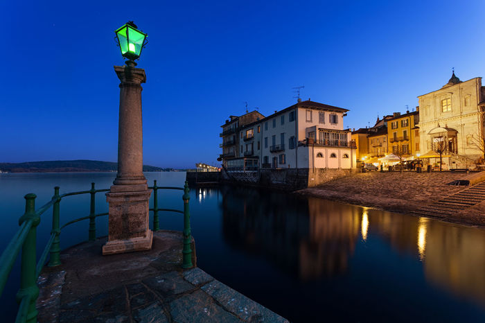 Reflections on the water by the lake at sunset. Arona, Lake Maggiore, Italy. Arona Lago Maggiore Blue Hour City City Light Cityscape Harbour Pier Water Reflections Architecture Arona Blue Illuminated Italy Jetty Lake Lake Maggiore Lakeside Landscape Lighting Long Exposure Pillar Sunset Travel Destinations Vacation Waterfront