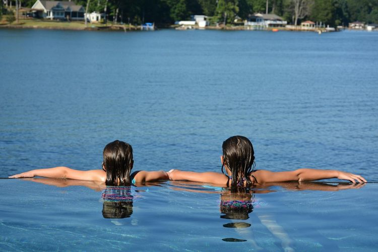Rear view of girls swimming in infinity pool