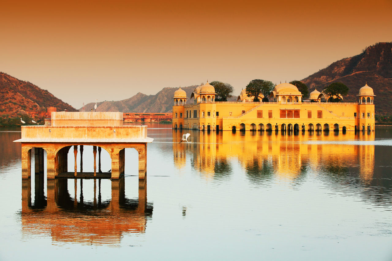 built structure, architecture, mountain, water, mountain range, reflection, clear sky, no people, day, nature, bridge - man made structure, lake, waterfront, outdoors, building exterior, travel destinations, scenics, sunset, beauty in nature, sky