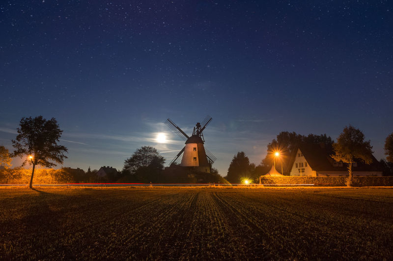 Illuminated traditional windmill on field against sky at night