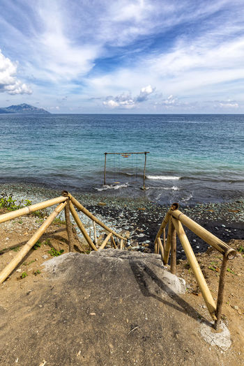 Steps leading down to a swing at Blue Stone Beach in Flores, Indonesia. ASIA Batu Ende INDONESIA Indonesian Rural Tourist Travel Trip Adventure Attraction Beach Biru Destination East Nusa Tenggara Flores Outdoor Pengajawa Pentai Savu Sea Southeast Stone Tourism Vacation