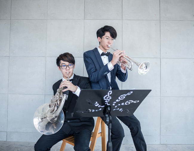 Students wearing suit playing musical instrument against wall