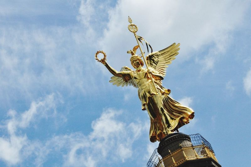 Gold Victoria Sculpture On Top Of Berlin Victory Column Against Sky