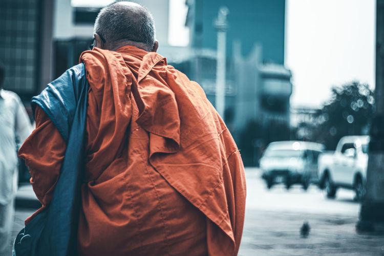 Rear view of monk walking on road in city