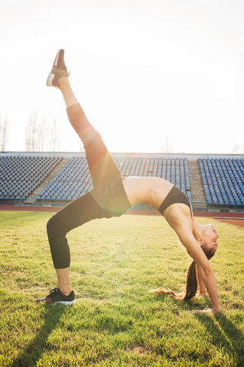 Full Length One Person Grass Leisure Activity Lifestyles Exercising Real People Healthy Lifestyle Day Sport Sunlight Nature Vitality Balance Wellbeing Plant Handstand  Flexibility Sky Skill  Outdoors Human Arm Arms Raised Effort Stretching