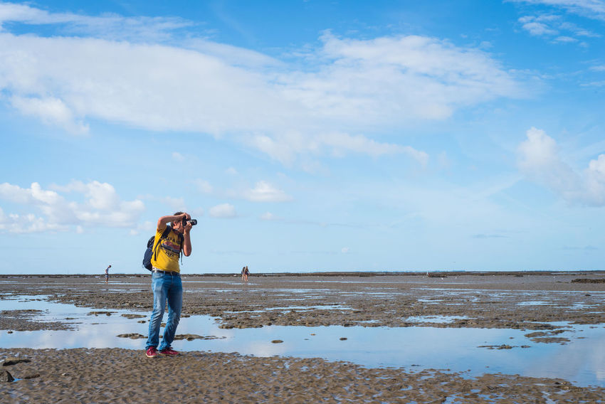 Water Sky Cloud - Sky Beach One Person Real People Sea Standing Beauty In Nature Leisure Activity Scenics - Nature Land Full Length Lifestyles Day Tranquility Non-urban Scene Nature Casual Clothing Horizon Over Water Outdoors Photographer Tourist Photographing Low Tide Coast Idyllic Coastline Sand Sandy Beach