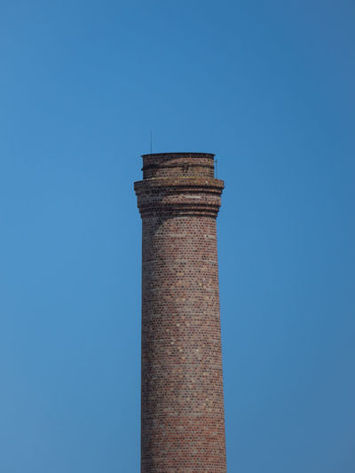 Low angle view of brick smoke stack against blue sky