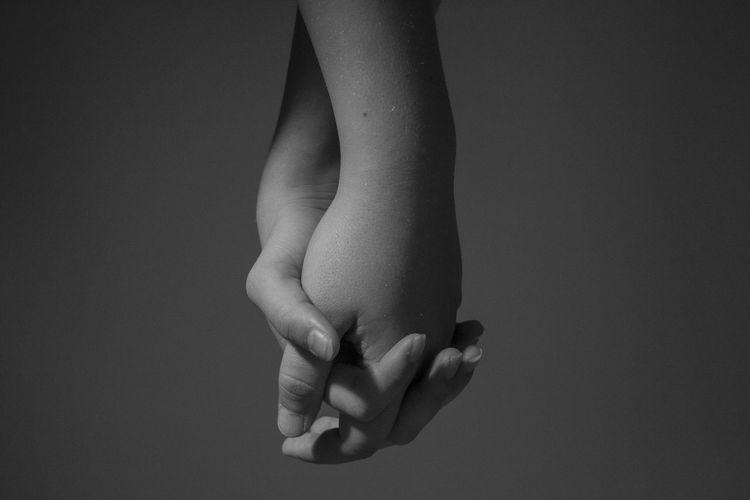 Cropped image of people holding hands against gray background