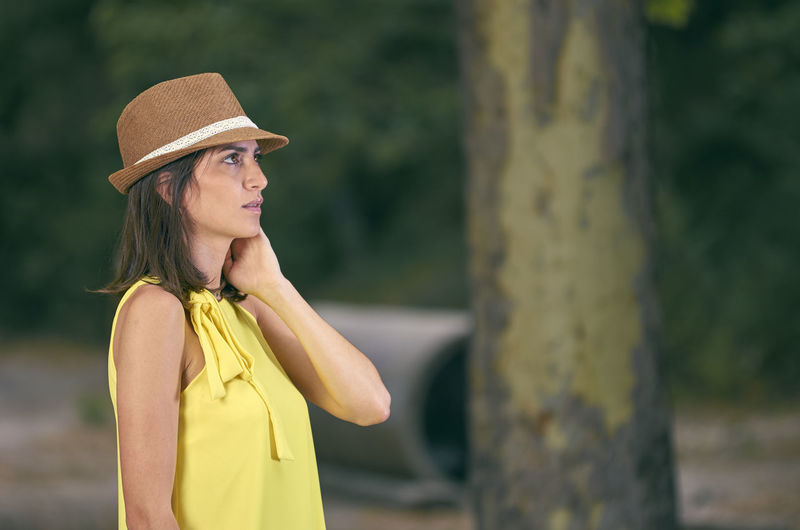 Attractive and fashionable young woman with a yellow dress in nature Beautiful Dress European  Fashion Happiness Hat Nature Peace Positive Relaxing Woman Attractive Cheerful Enyoing Female Hipster Lifestyles Model Modeling One Person Outdoors People Portarit Yellow Young Adult