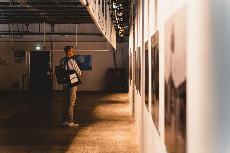 Berlin Photo Week 2018 Berlin Photo Week BPW18 EyeEem Full Length One Person Real People Architecture Casual Clothing Indoors  Standing Illuminated Building Young Adult Lifestyles Men Mid Adult Leisure Activity Built Structure Adult Young Men Lighting Equipment