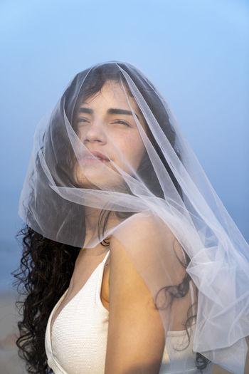 Woman with veil against sky