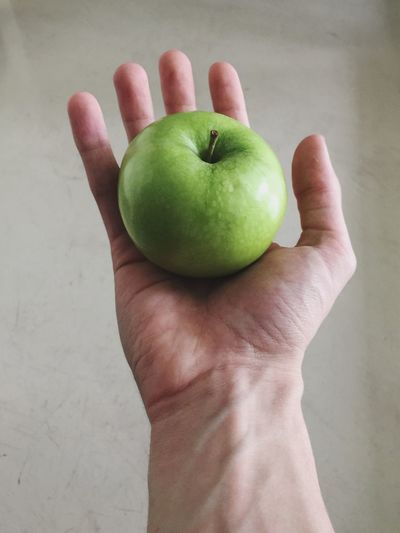 Close-up of cropped hand holding green apple