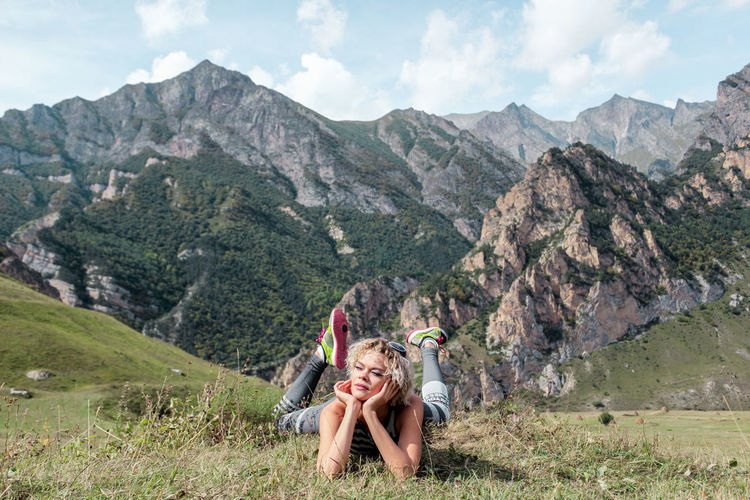 Young woman lying on front at field against mountains