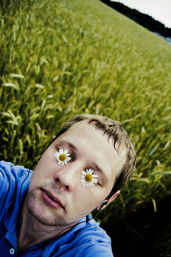 Close-Up Of Man With Eyes Covered By Flowers While Listening To Music On Field