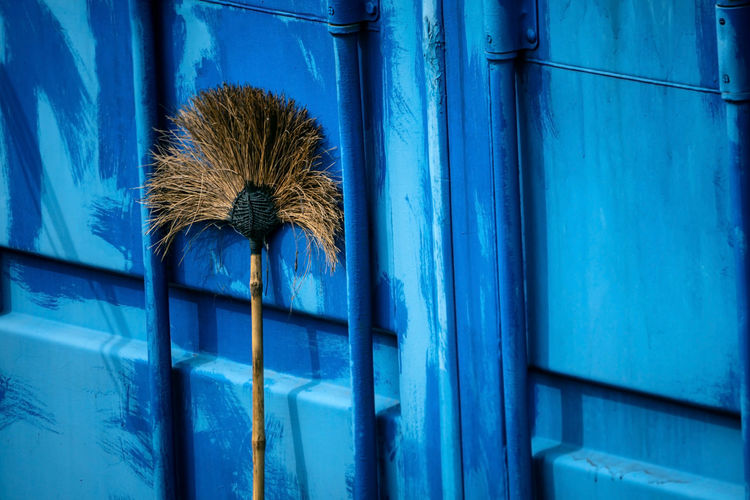 Hard broom leaning up against blue metal wall of container house, closeup and selective focus. Blue No People Cleaning Broom Cleaning Equipment Day Hygiene Window Wood - Material Wall - Building Feature Architecture Building Exterior Close-up Outdoors Built Structure Building House Clean Broomstick Düster Housecleaning Sanitation Simple Tools Typical