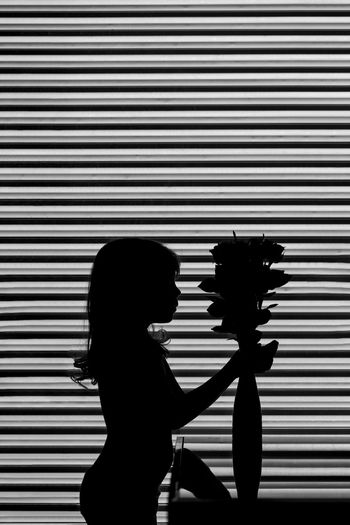 Girl of 5 years old is staying close to the vase with roses. black and white