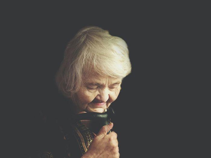 Senior Woman Holding Walking Cane Against Black Background