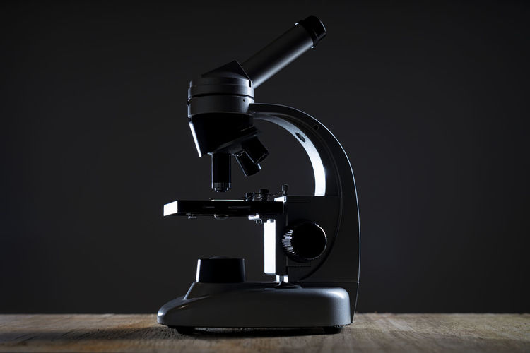 Microscope on table against black background