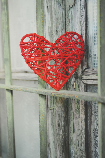 Close-up of red heart shape on wooden fence