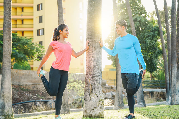 Smiling young couple exercising in park