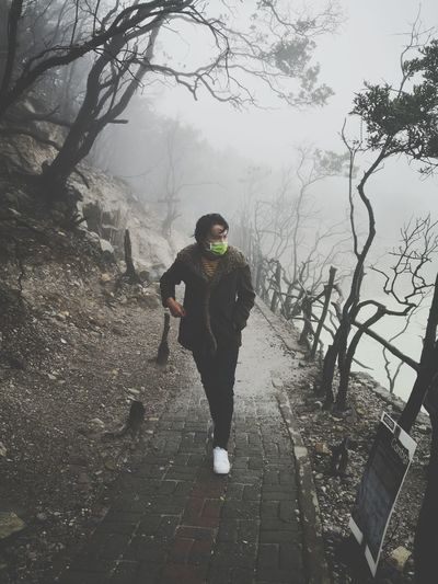 Full length of man wearing surgical mask while walking on footpath during winter