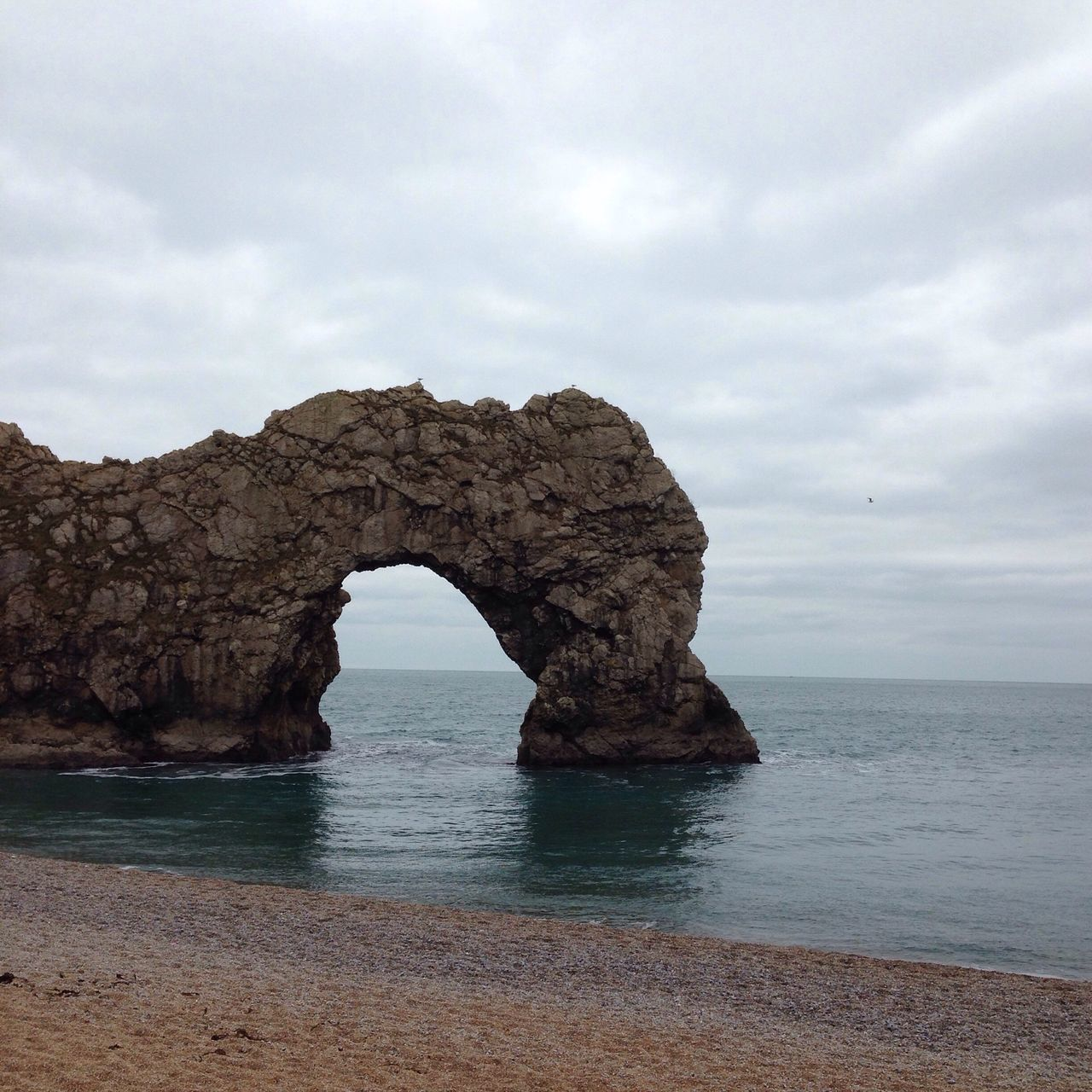 Rock Formation At Durdle Door Against Cloudy Sky