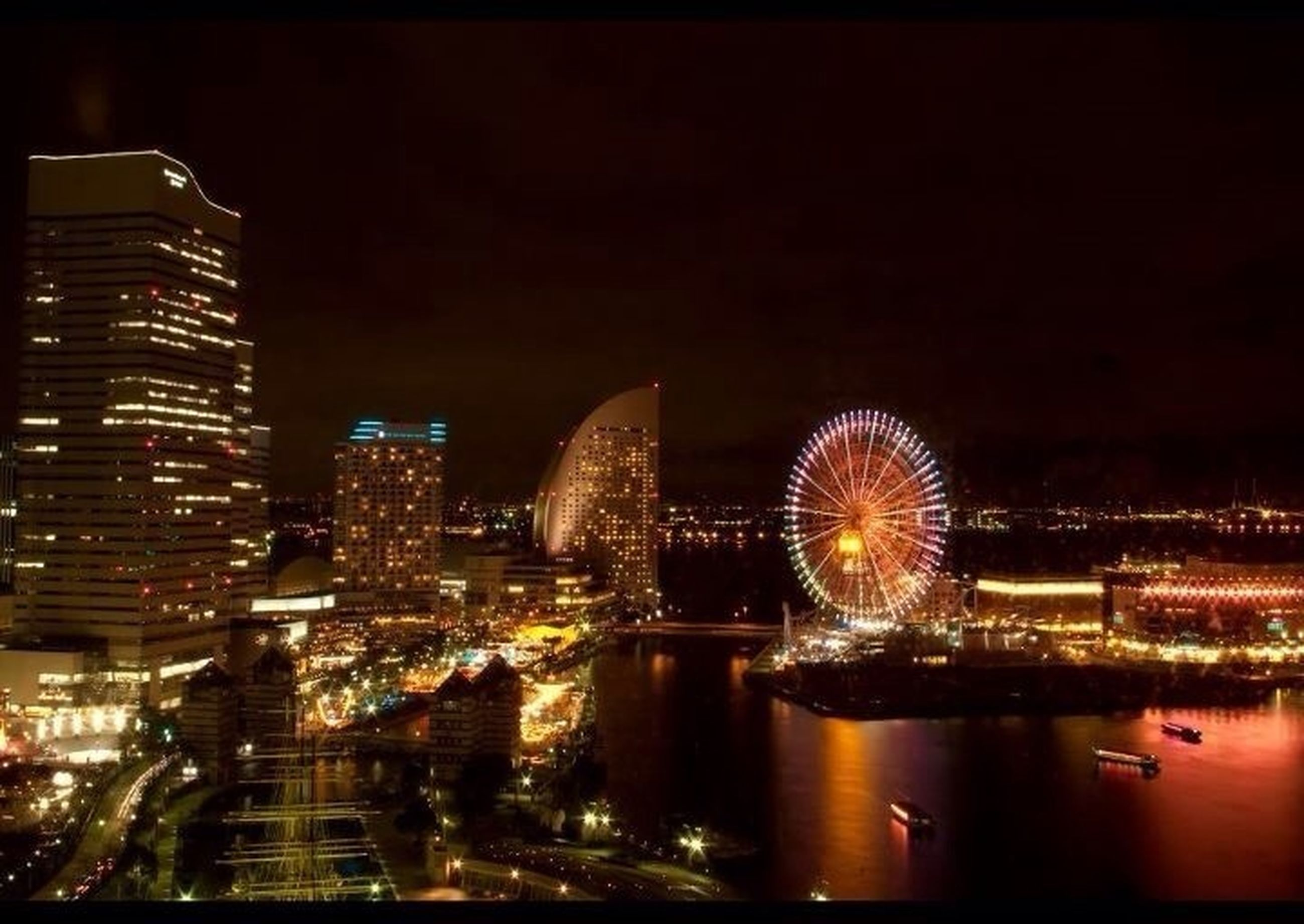 illuminated, night, city, architecture, building exterior, built structure, water, cityscape, reflection, river, modern, waterfront, city life, skyscraper, travel destinations, ferris wheel, capital cities, sky, long exposure, clear sky