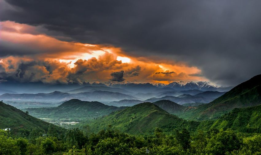 Scenic view of clouds over mountains during sunset
