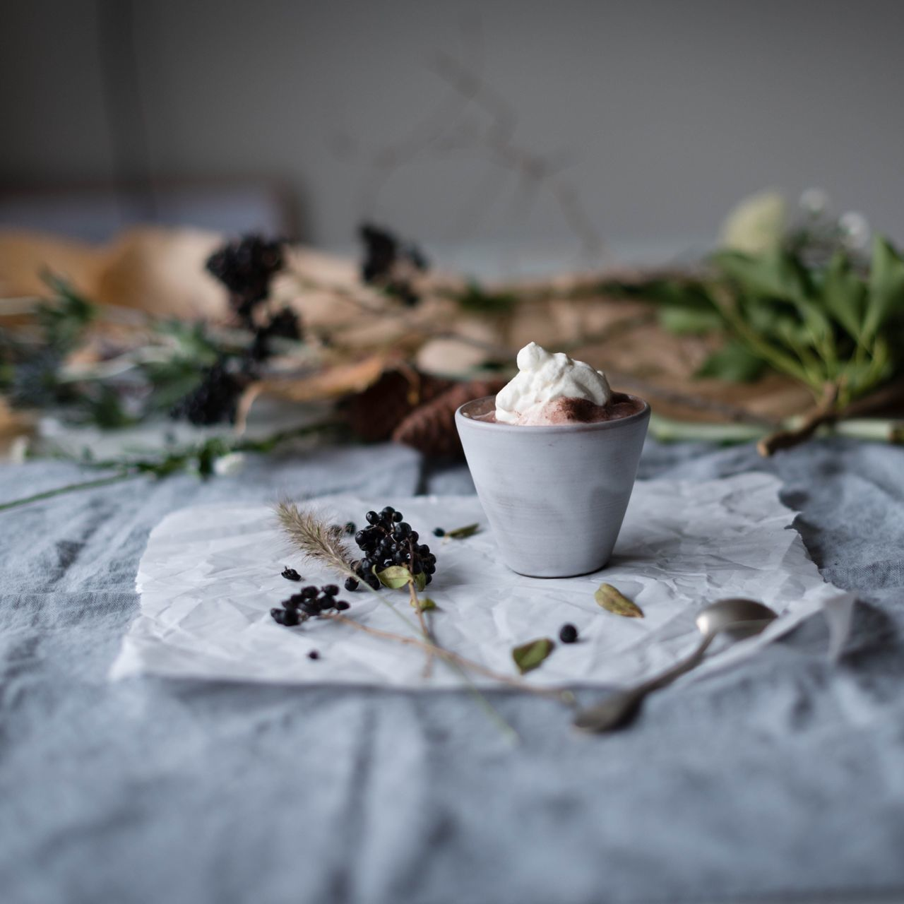 Hot chocolate in cup and food on tissue paper over table