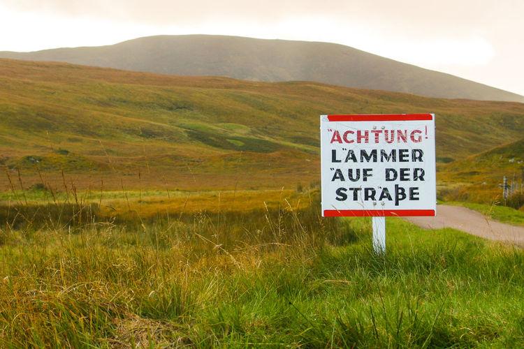 Information sign on landscape against sky
