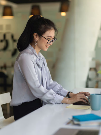 Side view of businesswoman working on computer in office