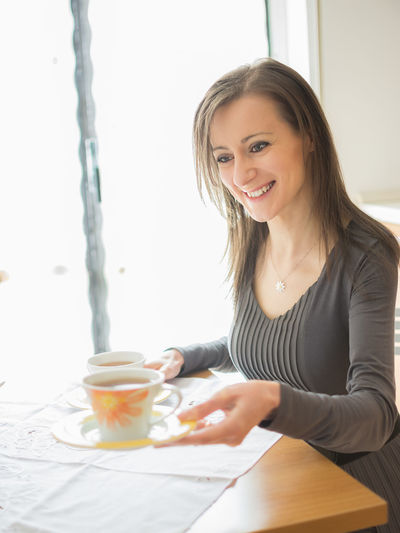 Smiling Woman Giving Tea At Home