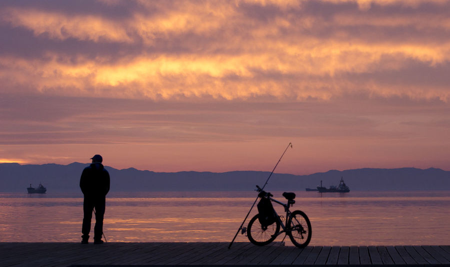 Man Vacations Beauty In Nature Bicycle Cloud - Sky Day Fishing Full Length Lake Lifestyles Mode Of Transport Nature One Person Outdoors People Real People Scenics Silhouette Sky Sunrise Sunset Tranquil Scene Tranquility Transportation Water The Traveler - 2018 EyeEm Awards