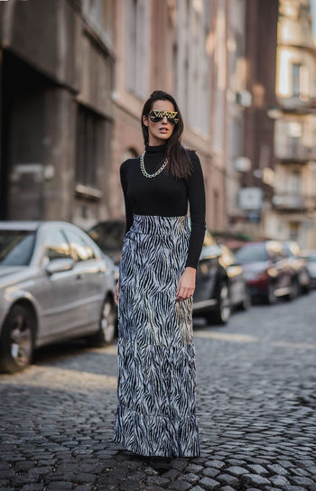 Fashionable woman standing on footpath in city