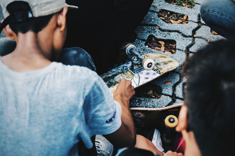 People repairing skateboard on street