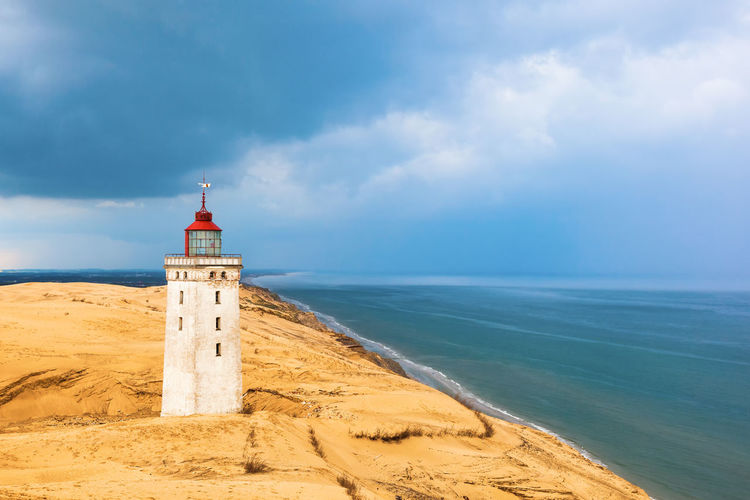 Rabjerg mile a lighthouse on the Danish coast with storms clouds in the sky Coastline Råbjerg Mile Stormy Weather Weather Architecture Beach Buried Cloud - Sky Coast Horizon Horizon Over Water Land Lighthouse No People Rain Clouds Sand Sand Dune Sandy Scenics - Nature Sea Sky Storm Cloud Tower Travel Destinations Water