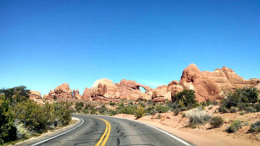 Road by rock formations at arches national park