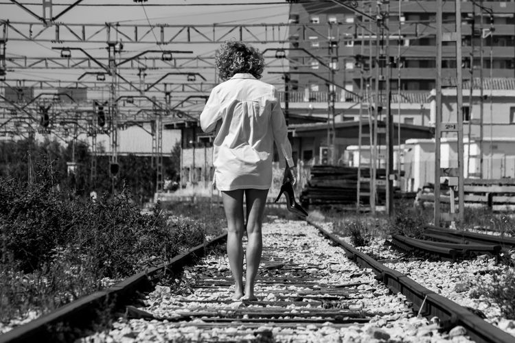 Rear view of woman standing on railroad tracks
