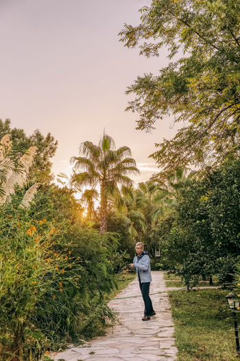 Rear view of woman standing on footpath by palm trees against sky