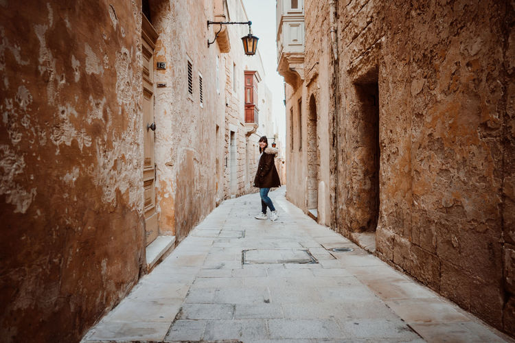 Portrait of young woman walking in alley