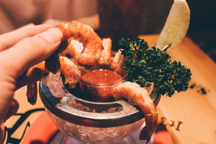 Cropped image of hand holding prawns