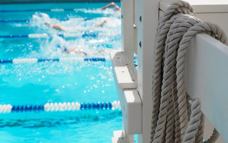Close-up of ropes on railing by swimming pool