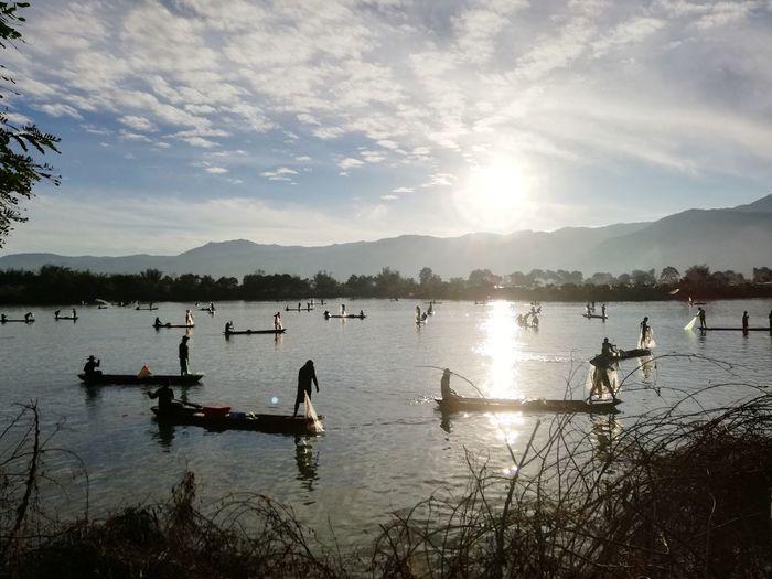 Silhouette Fishermen Fishing In Lake Against Sky