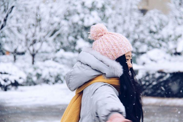 Woman Wearing Warm Clothing Enjoying Snowfall