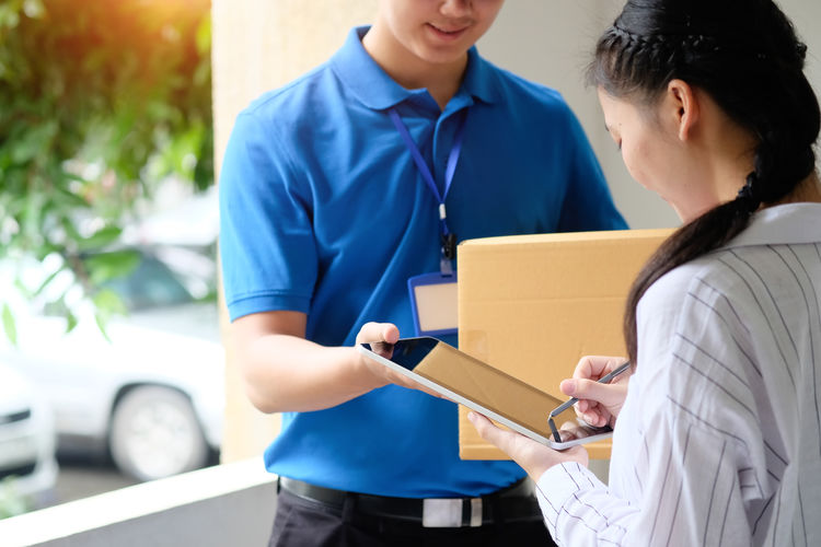 Woman signing in digital tablet held by delivery man at home