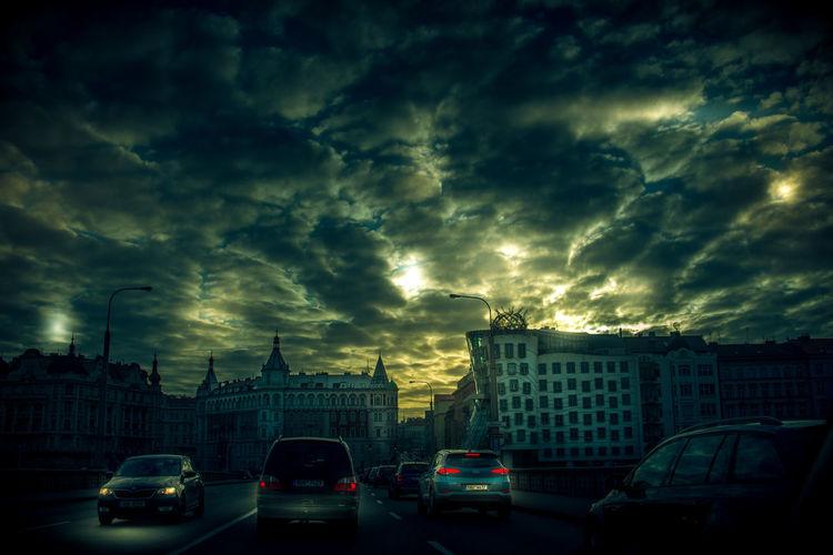 Cars on city street against dramatic sky