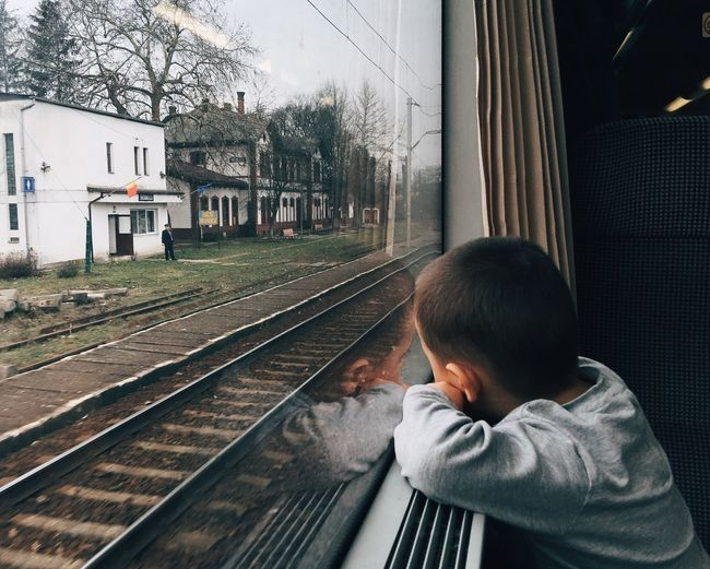 Side View Of Boy Looking Through Window In Train