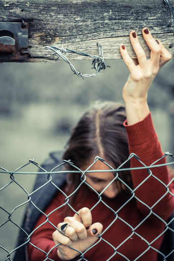 Woman in red sweater with dark manicured nails and heart-shaped ring pushing against metal fence.