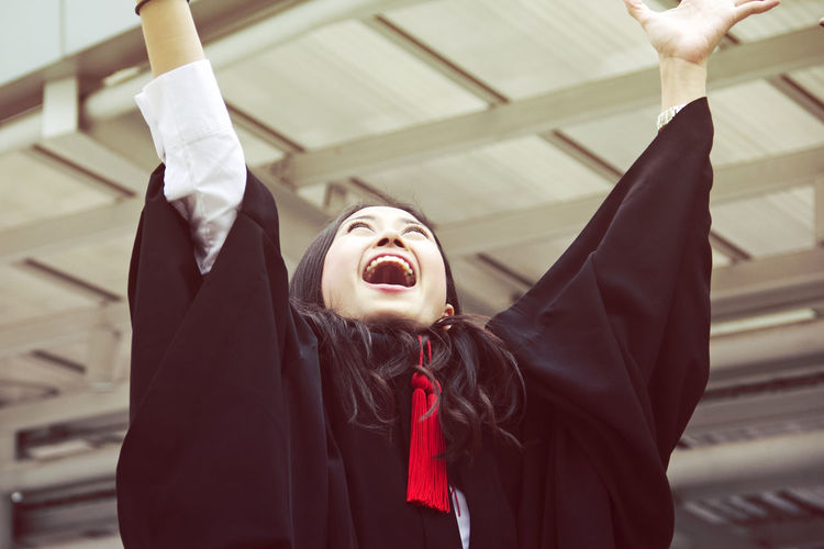 Cheerful Young Woman In Graduation Gown With Arms Raised