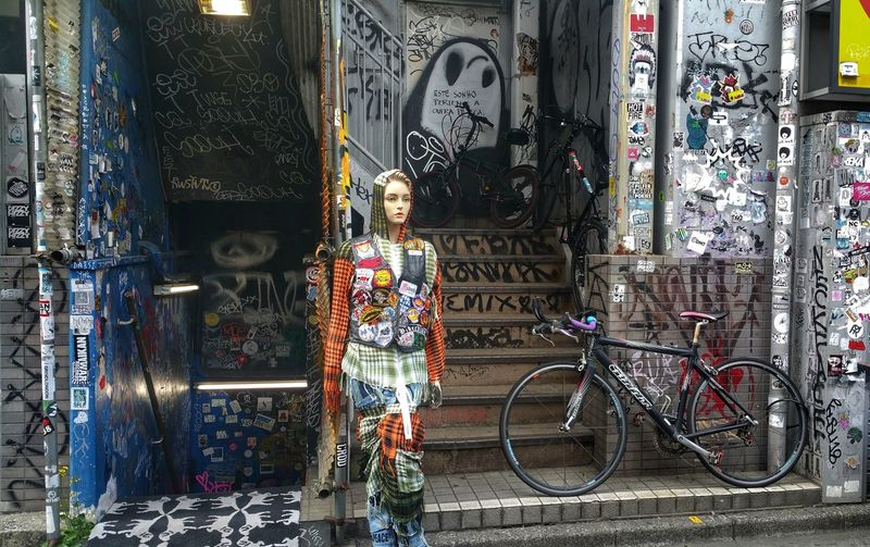 Full length of woman standing by graffiti on store
